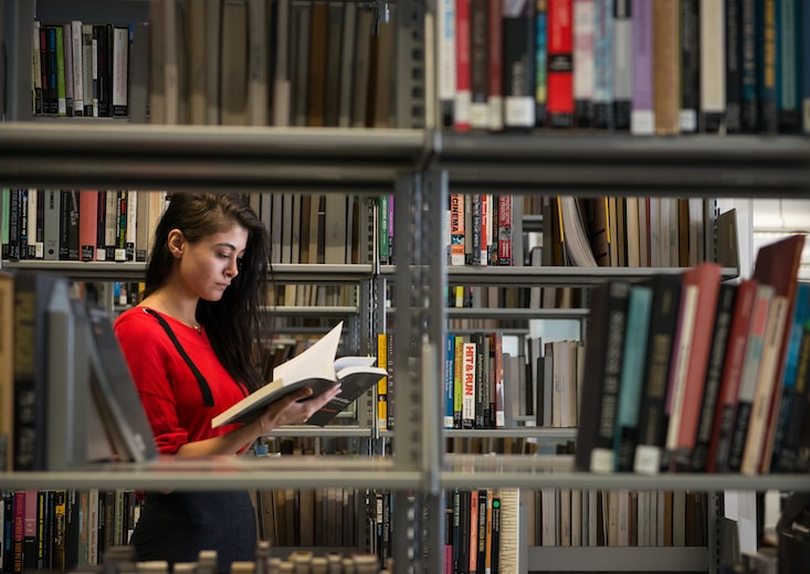 Woman studying in a library as she works to earn her online MBA